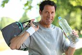 picture of transpiration  - 50 years old man drinking man after he did sport - JPG