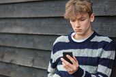 Sad depressed thoughtful male boy teenager blond child outside using mobile cell phone for texting o poster