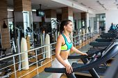 Profile view of attractive young woman exercising on treadmill while having intensive workout at spa poster