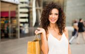 Beautiful woman holding a bag in a shopping mall poster