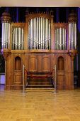 pic of pipe organ  - Massive wooden pipe old organ with many metal pipes and ornate finishing - JPG