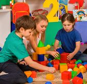 Children playing in kids cubes indoor. Lesson in primary school. Body part of girl and boy together  poster
