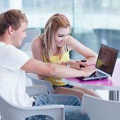 dos estudiantes universitarios que se divierten estudiar juntos, usando una computadora portátil (DOF, de poco color tonificada
