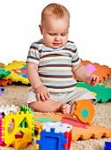 Baby making puzzle. Child jigsaw develops children. Kid holding big pieces and sitting on floor. Por poster