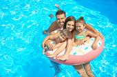 Happy family with inflatable ring relaxing in swimming pool poster