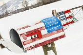 An American Flag mailbox is covered with snow after a winter storm. poster