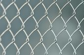 Silvery Fence Made Of Metal Mesh Of The Slab, On A Gray Fuzzy Background. Close-up poster