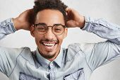Cheerful Overjoyed Dark Skinned Fashionable Male In Trendy Round Spectacles, Wears Stylish Shirt, Ke poster