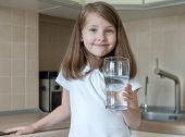 Portrait Of A Little Caucasian Baby Girl Holding A Glass Of Tap Clean Water. Kitchen Faucet. Cute Ki poster