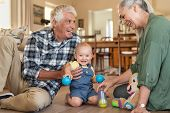 Smiling grandchild with grandparents playing with balls at home. Happy grandson with grandmother and poster