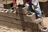 pic of cinder block  - Migrant worker building cinder block wall in desert setting - JPG