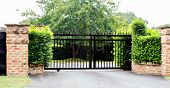 Black Metal Driveway Property Entrance Gates Set In Brick Fence With Garden Shrubs And Trees In Back poster