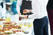 Catering service. man take snack from food court table at event poster