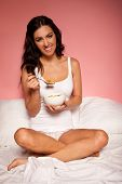 Smiling attractive brunette eating a bowl of healthy breakfast cereal sitting cross-legged in her bed