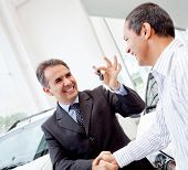 Salesman handling keys to a man after buying a car
