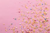 Sprinkles On Pink Background - Assorted Colourful Cake Topping Sprinkles Sprayed On Pink On Bottom C poster