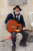 JERUSALEM - FEBRUARY 23: A classical guitarist takes a break from busking February 23, 2012 in Jerus