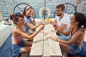 Happy friends toasting drinks on the yacht deck and laughing. Cheerful men and woman partying on a b poster