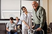 Portrait of senior man being assisted by female nurse to walk Zimmer frame with people sitting in ba