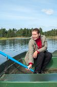 Happy Smiling Caucasian Woman In Row Boat Holding Paddle