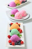 three plates with ice cream and fruit