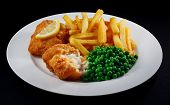 Close Up Of Fish And Chips With Peas And A Slice Of Lemon.