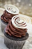 Chocolate cupcake with chocolate mousse cream icing on grunge wooden background with bokeh lights