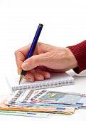 Hand, Pen, Notebook And Money