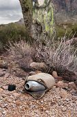 An old, vintage hiking canteen lies in a parched, dry desert, empty.