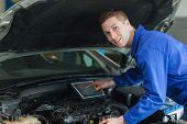 Portrait of confident mechanic by car using digital tablet