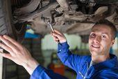 Portrait of male mechanic working under car
