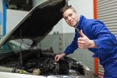 Portrait of mechanic gesturing thumbs up as he checks oil level of car