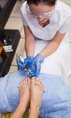 Nail technician removing callus at feet in nail salon