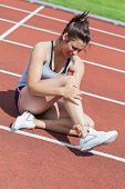 Female runner with ankle injury on track