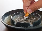 Closeup Hand Crushes Cigarette In Ashtray And Smoke On The Table