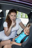 Mother Showing Shh Gesture When Daughter Asleep In Car Safety Seat