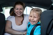 Laughing Mother With Small Daughter In Car Safety Seat