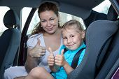 Mother And Child Showing Thumb Up Gesture In Car Safety Seat