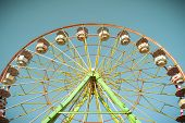 stock photo of wind wheel  - Ferris wheel goes around in a sunny blue sky - JPG