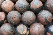 stock photo of cannon-ball  - stack of old colonial rusty cannon balls - JPG