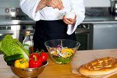 Chef Sprinkling Salt On Vegetables