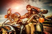 stock photo of biker  - Biker girl in a leather jacket on a motorcycle looking at the sunset - JPG