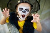 stock photo of antichrist  - Portrait of cute girl in Halloween costume looking at camera with frightening expression - JPG