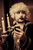 Modern prince. Young in eighteenth century image posing with candle