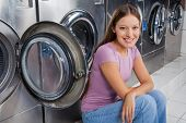 Portrait of beautiful young woman sitting against washing machines in laundry