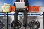 Low section of young businessman using laptop while sitting on washing machine