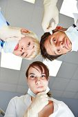 Dentist and dental assistants looking pensive at patient POV