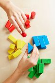 Two female hands sorting building blocks by color