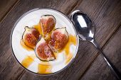 Greek yogurt with figs and honey, in a glass bowl over old wood background