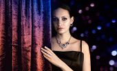 Beautiful woman behind the curtain on dark background